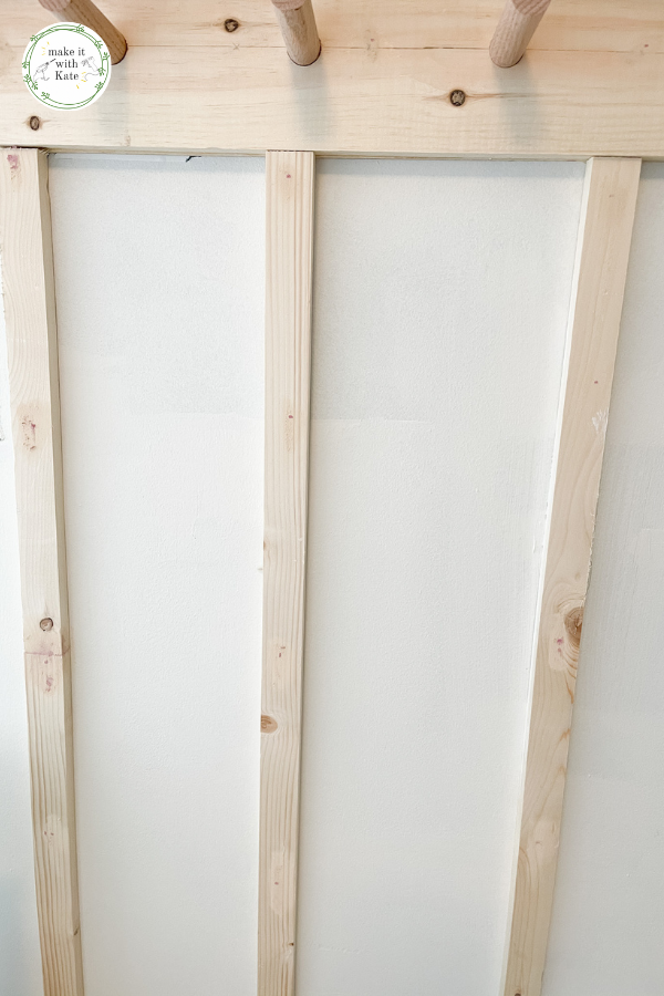This DIY board and batten with a peg rail top makes the perfect addition to an entryway or mud room design. Super easy to make! #diymudroom #diyboardandbatten #millwork #woodworking #housedesign